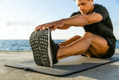 sporty adult man with wireless earphones stretching on seashore