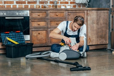 professional repairman fixing vacuum cleaner