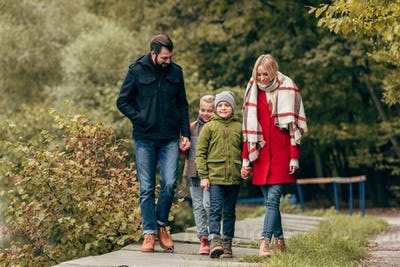 happy young family holding hands and walking in autumn park