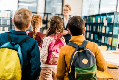 back view of schoolchildren with backpacks looking at librarian in library