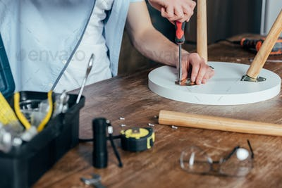 cropped shot of man repairing stool with screwdriver