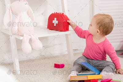 adorable kid taking first aid kit in children room