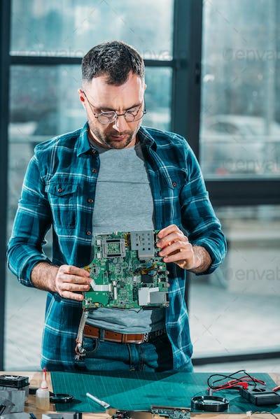 Hardware engineer checking circuit board