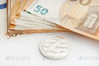 Litecoin coin and Euro banknotes