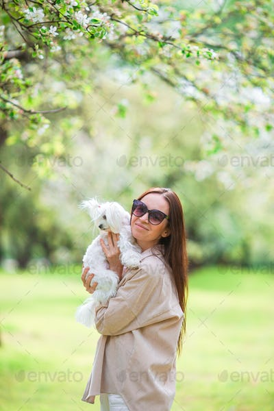 Woman playing and hugging puppy in the park