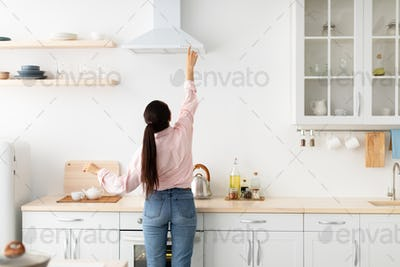 Woman select mode on cooking hood in kitchen