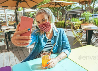 Girl in bar taking a selfie with a smartphone with her face mask on