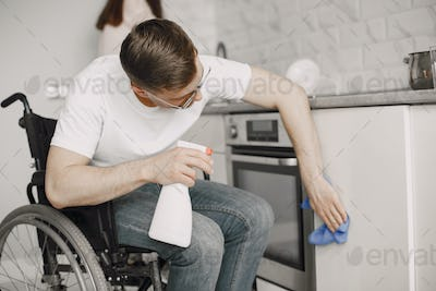 Young Handicapped Man On Wheelchair Cleaning Stove