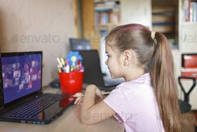 Distant education, online class meeting. Schoolchild studying math during online lesson at home