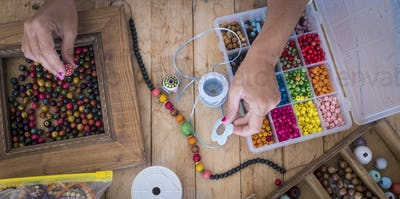 Top view of woman doing jewelry beads accessories with colorful cords - home work job