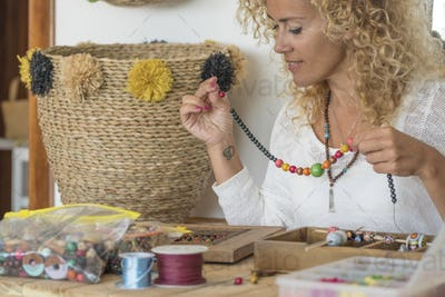 Young adult woman produce beads jewels at home at the table - modern home work