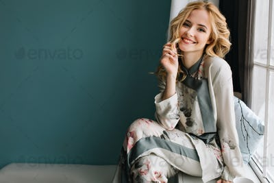 Beautiful young woman with long blonde wavy hair sitting on window sill in room with turquoise wall.