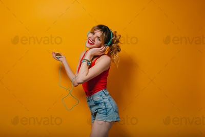 Pretty girl chilling on orange background in studio. She wears red T-shirt, blue headphones on on th