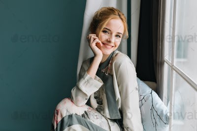 Portrait of smiling, happy blonde girl next to the window, relaxing in the morning, having good time