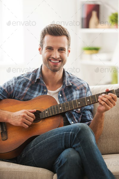 Relaxing at home. Cheerful young man playing the guitar while sitting on sofa