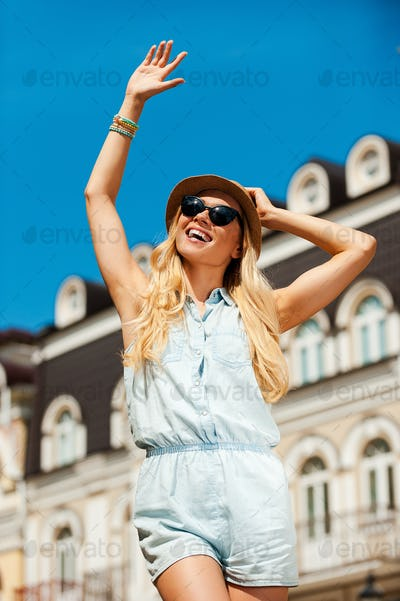 Hi there! Low angle view of cheerful young woman waving and looking away while standing outdoors