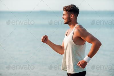 Feeling good and keeping fit. Side view of smiling young muscular man running along the riverbank