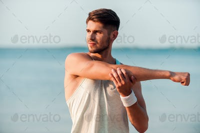 Man worming up. Confident young muscular man stretching his arms while standing at the seaside