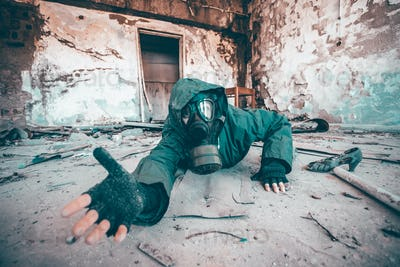 Dramatic portrait of a woman wearing a gas mask in a ruined building.