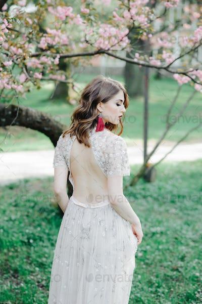 very beautiful girl the bride under a veil, beige wedding dress near the tree Sakura