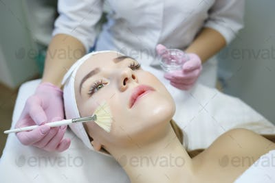 Cosmetologist does face peeling of a beautiful woman. Women's cosmetology in the beauty salon