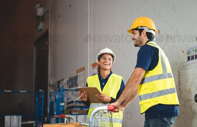 warehouse workers logistic team wearing hardhats to working in aisle between tall racks