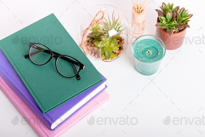 Books, eyeglasses and succulents on pink, top view