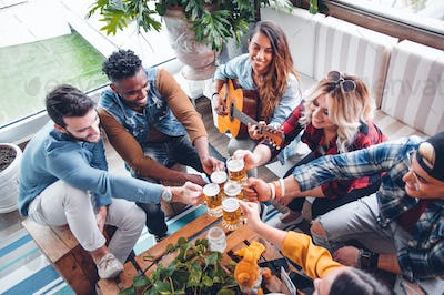 Group of mixed people having fun cheering home brew and playing guitar