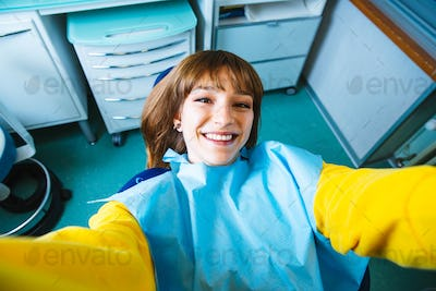 Beautiful happy young woman sitting in medical dentist center taking a selfie