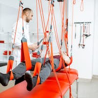 Physiotherapist doing spine treatment with suspension equipment for a man