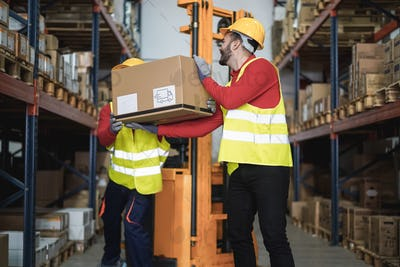 Industrial workers loading delivery box inside warehouse store - Focus on right man