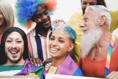 Multiracial gay people having fun at pride parade with LGBT flags and banners