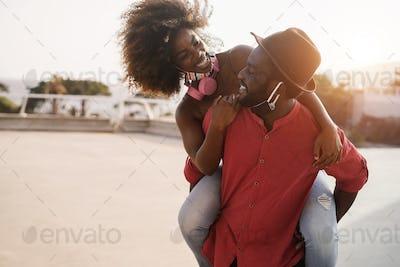 African couple having fun outdoors wearing face masks - Focus on man face