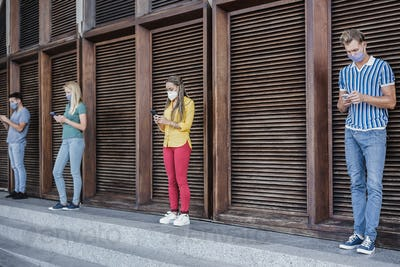 Young multiracial friends wearing protective masks while using mobile phone