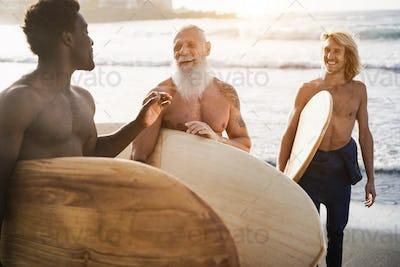 Multi generational surfer men having fun on the beach