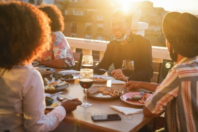 Happy multiracial friends eating and drinking wine together with safety masks