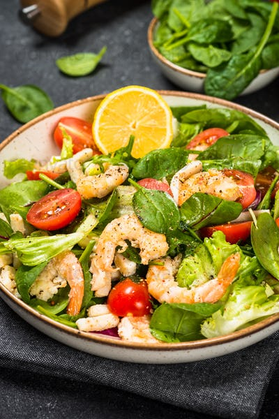 Shrimp salad with green leaves at stone table