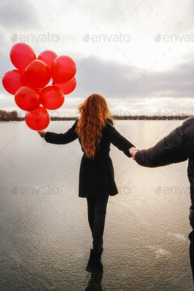 Love couple with red balloons outdoor