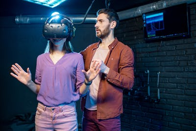 Woman trying virtual reality with man assistant