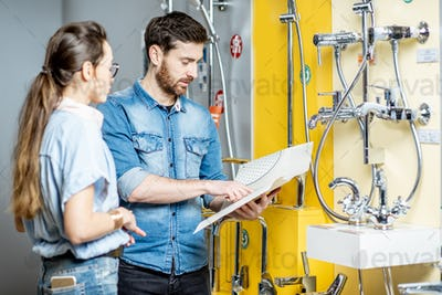 Couple choosing shower faucet in the shop