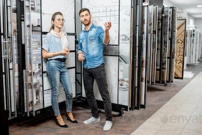Couple choosing ceramic tiles in the shop