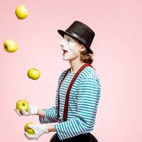 Pantomime juggling with apples on the pink background