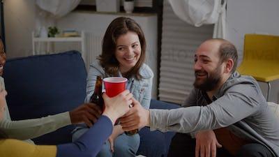 Multi cultural friends cheering beer bottles during wekeend party