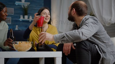 Multiracial friends laughingwhile enjoying night party drinking beer