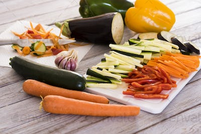 Fresh vegetables on a wooden table with a mix of sliced carrots, zucchini, eggplant and peppers