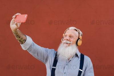 Happy senior hipster man listening music on smartphone app outdoors - Tech, elderly lifestyle