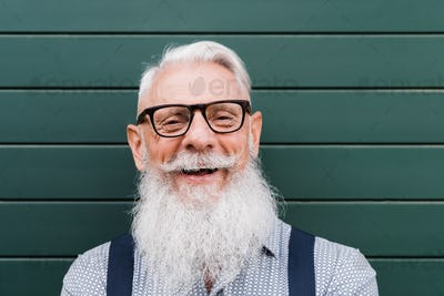 Happy hipster senior man smiling on camera with green background - Focus on face