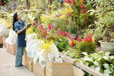 Woman searching plant in greenhouse