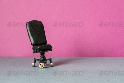 Comfortable black leather office chair on a pink gray background