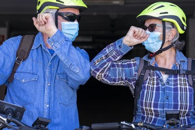 Two people bump elbows before bicycle excursion. Stop shake hands because of coronavirus pandemic